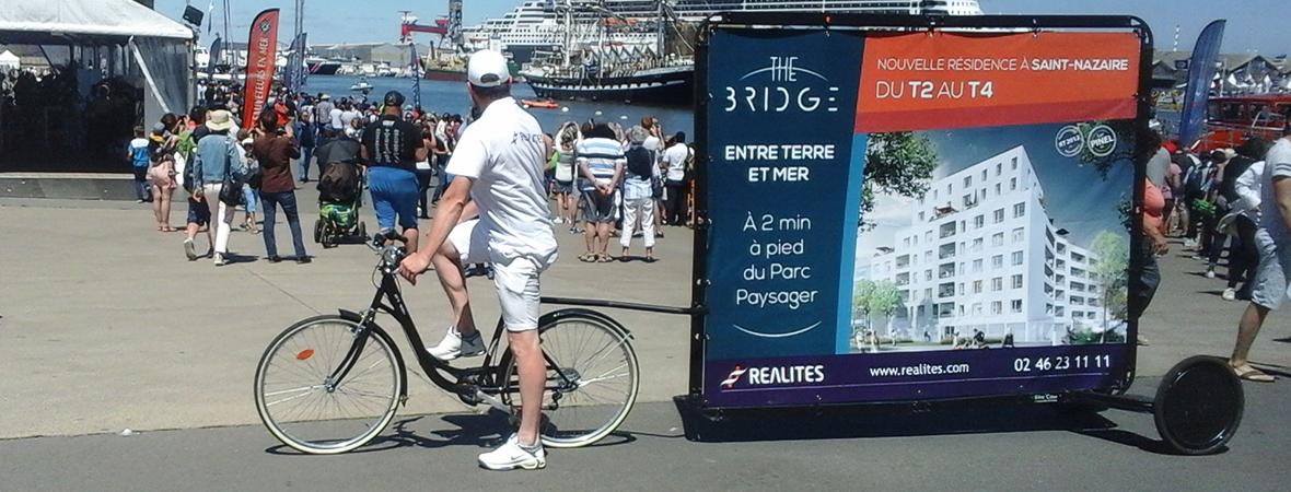 Promoteur Realites - street marketing en Bike'Com - NON STOP MEDIA Atlantique