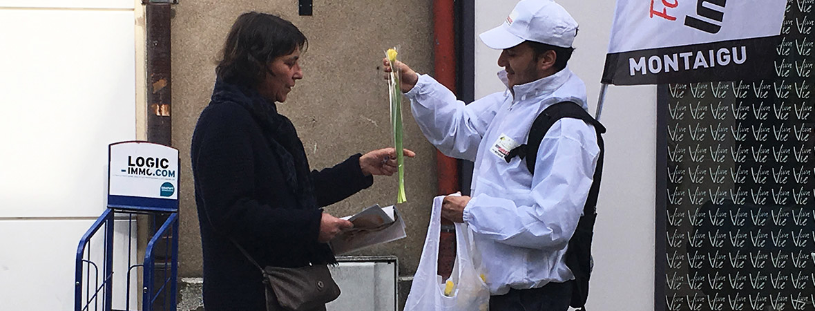 Street marketing : Animateur aux couleurs d'Intermarché donne une fleur jaune à une passante - NON STOP MEDIA Atlantique