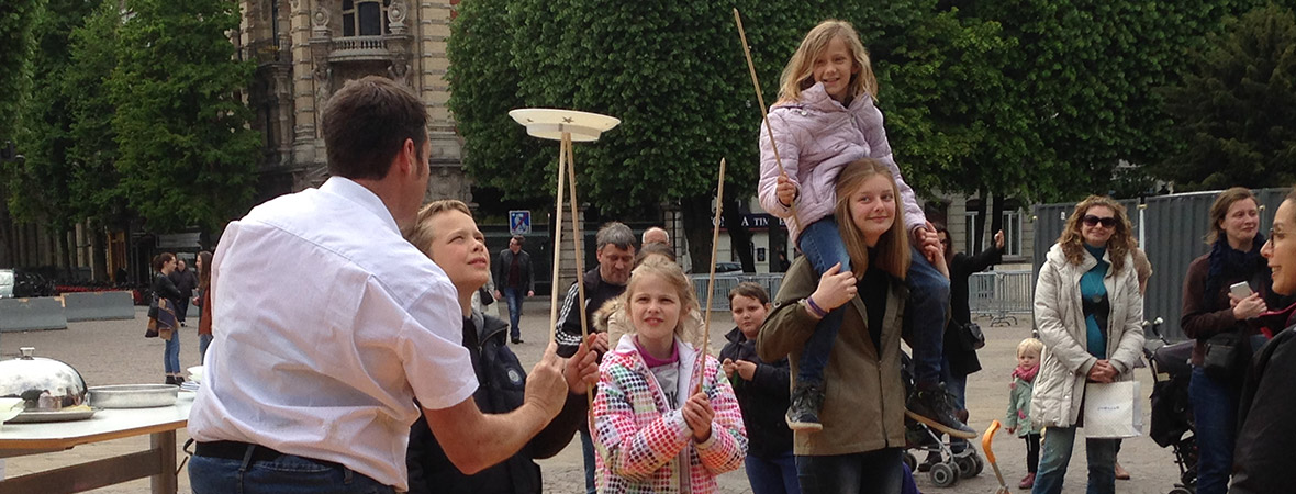 Street marketing : artiste de cirque performe devant un public dans la rue - NON STOP MEDIA Nord