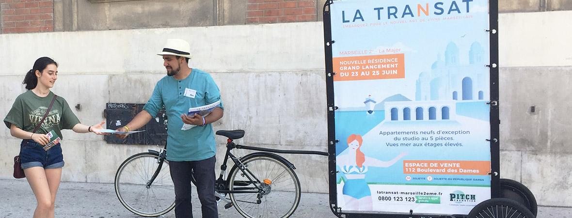Marketing de proximité : Animateur Bike Com' donne flyers aux passants NON STOP MEDIA PACA